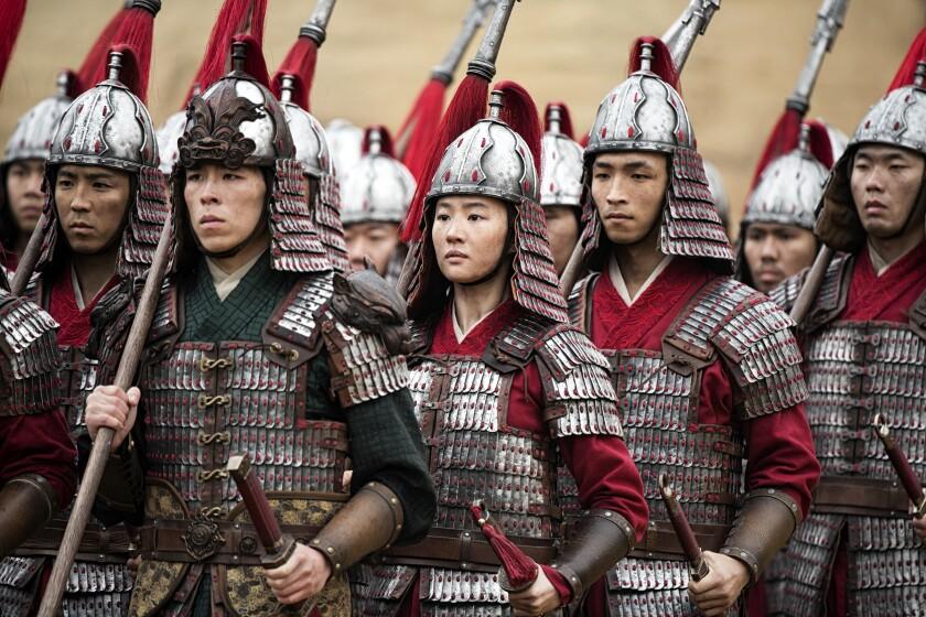 """From center, Mulan (Liu Yifei) and Honghui (Yoson An) in Disney's """"Mulan."""""""