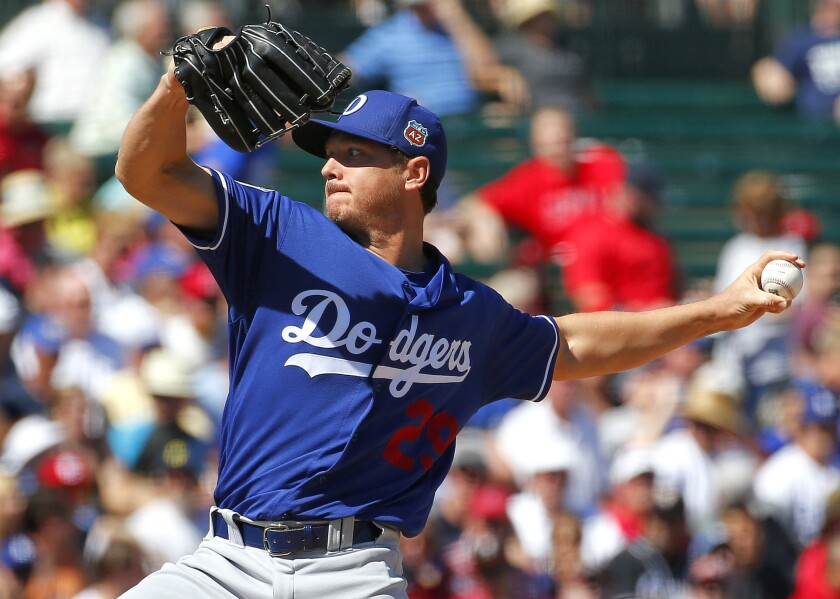 Dodgers starting pitcher Scott Kazmir throws against the Angels during the first inning of a spring training game.