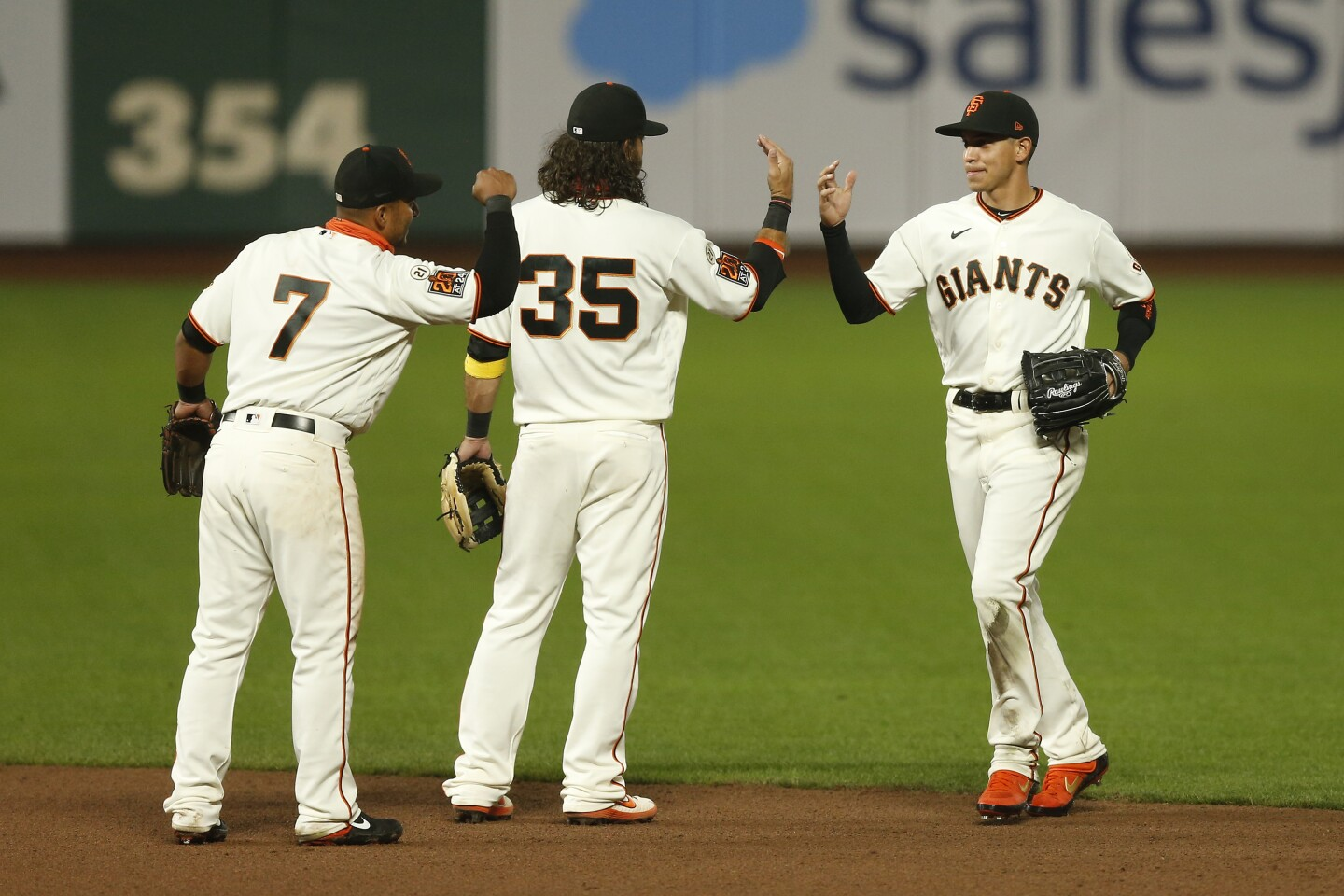 SAN FRANCISCO, CALIFORNIA - SEPTEMBER 09: Donovan Solano #7, Brandon Crawford #35 and Mauricio Dubon #1 of the San Francisco Giants celebrate after a win against the Seattle Mariners at Oracle Park on September 09, 2020 in San Francisco, California. (Photo by Lachlan Cunningham/Getty Images)