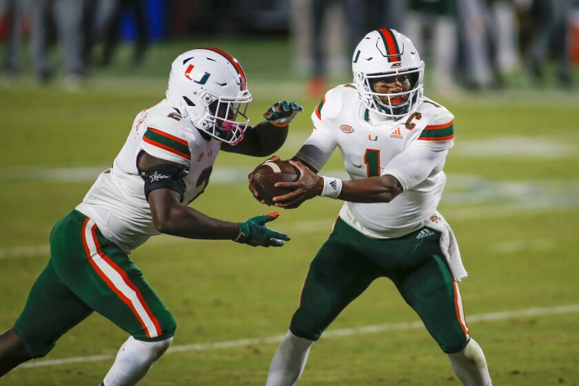 Miami quarterback D'Eriq King (1) hands off to running back Donald Chaney Jr. during the second quarter of the team's NCAA college football game against Duke on Saturday, Dec. 5, 2020, in Durham, N.C. (Nell Redmond/Pool Photo via AP)