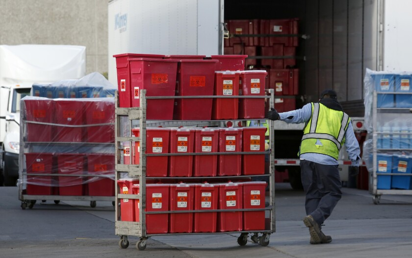 A worker at Stericycle pulls a cart stacked with containers of biohazardous waste.