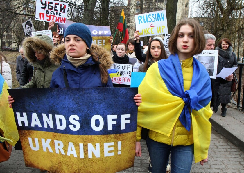 "Demonstrators wear the Ukrainian flag and hold posters reading ""Hands off Ukraine"" during a protest against Russia's intervention in Ukraine in front of the Russian embassy in Vilnius."