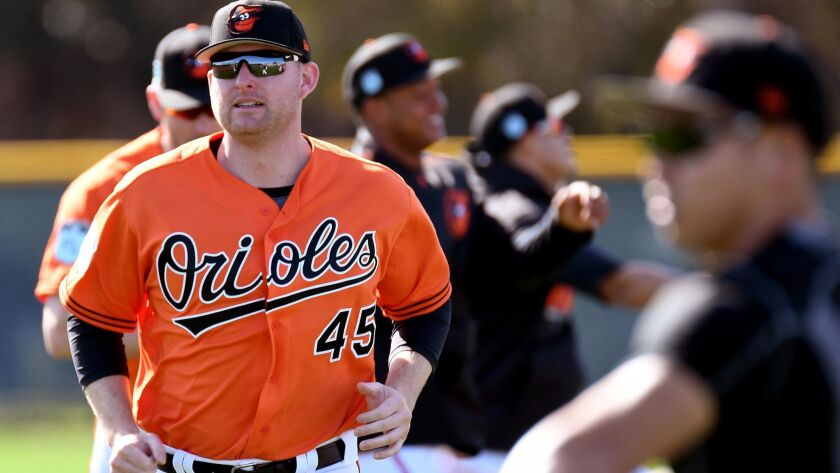 Orioles infielder Mark Trumbo (45) warms up during the spring training workout at Ed Smith Stadium.