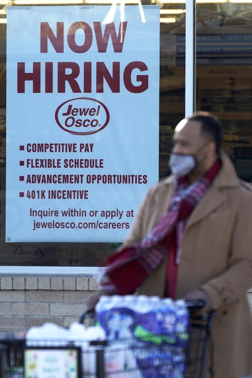 A now-hiring sign is shown as a shopper exits a grocery store Dec. 4 in Deerfield, Ill.