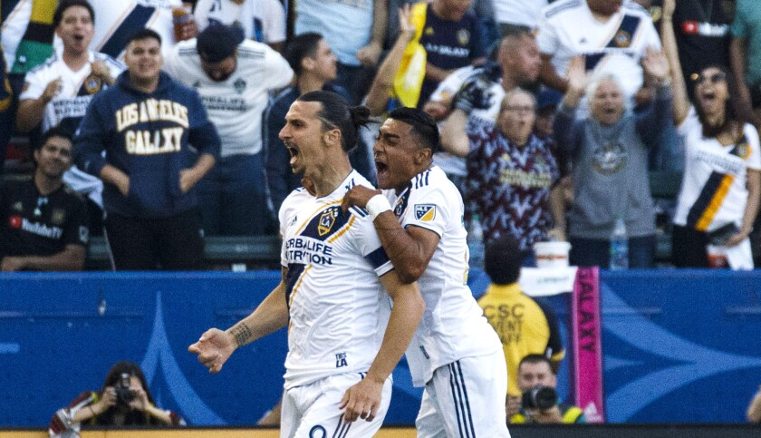 Galaxy forward Zlatan Ibrahimovic celebrates with defender Julian Araujo after scoring a goal in the first half of the game against LAFC on Friday night.
