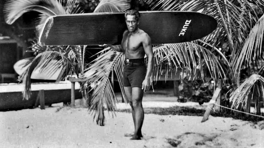 Duke Kahanamoku is pictured with his surfboard.He is the subject of aGoogle Doodle today.