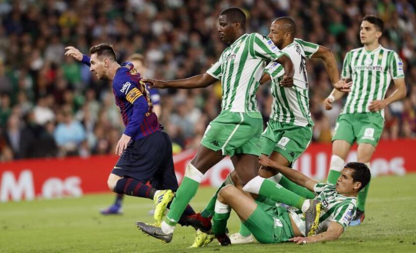 El delantero argentino del FC Barcelona, Leo Messi (i), tras golpear el balón ante los jugadores del Real Betis consiguiendo el segundo gol del equipo blaugrana durante el encuentro correspondiente a la jornada 28 de primera división que disputaron en el estadio Benito Villamarín, en Sevilla. EFE
