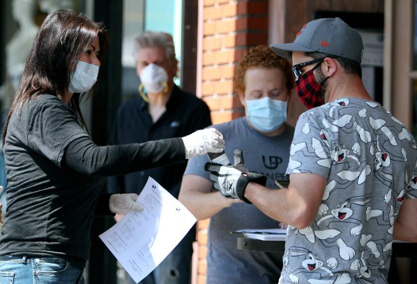 Cynthia Hutchinson, izquierda, entrega a Ryan Morrison una botella gratis de desinfectante de manos hecho con ginebra