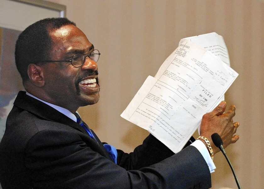 """Former boxer Rubin """"Hurricane"""" Carter holds up the writ of habeas corpus that freed him from prison, during a news conference held in Sacramento, Calif., in 2004. Carter, who spent almost 20 years in jail after twice being convicted of a triple murder he denied committing, has died at his home in Toronto at 76."""