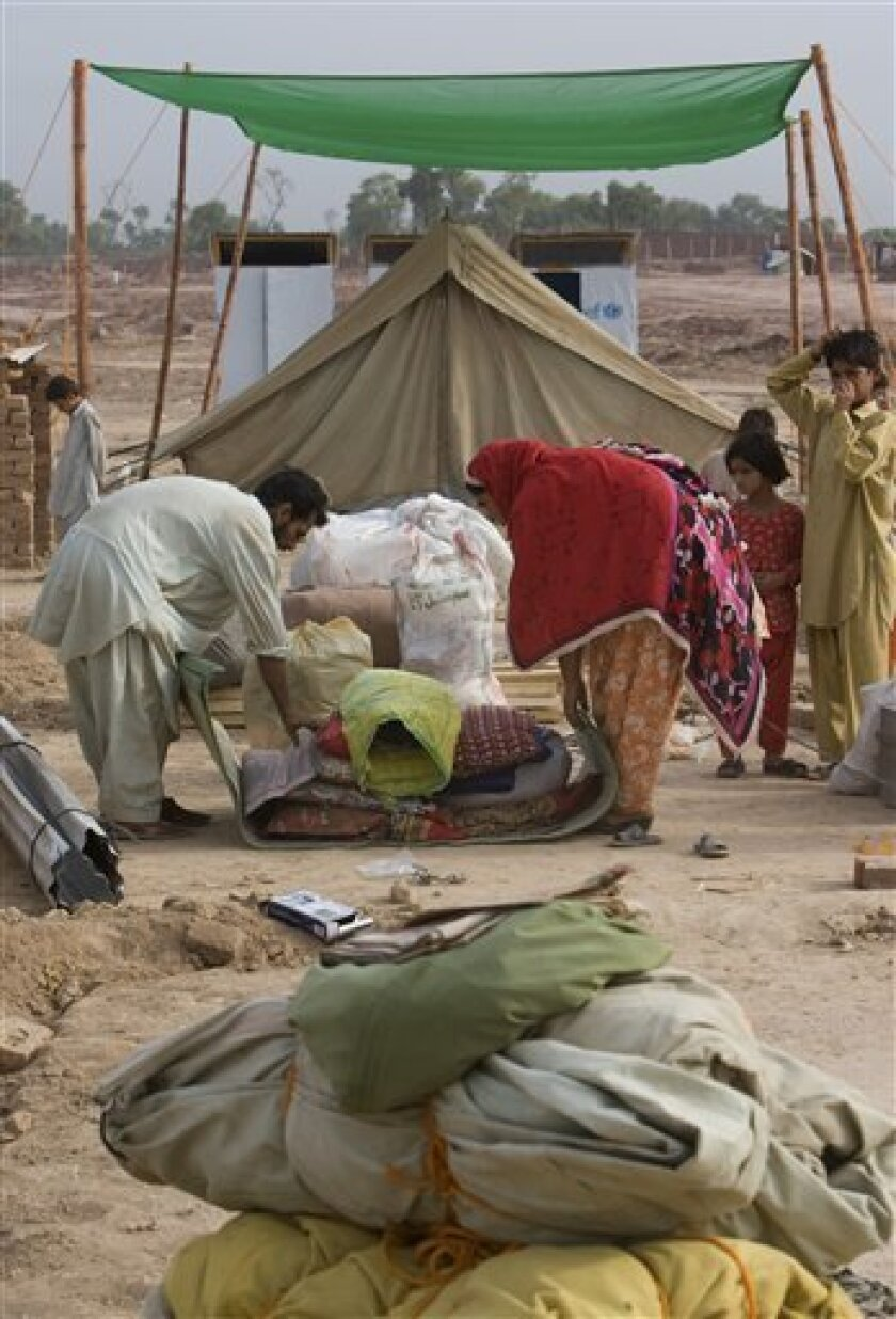 Pakistani displaced family pack their belongings as they prepared to return to their villages from Jalozai Internal Displaced camp near Peshawar, Pakistan, Monday, July 13, 2009. Pakistan start sending two million refugees to return to their homes in the Swat Valley. (AP Photo/Vincent Thian)