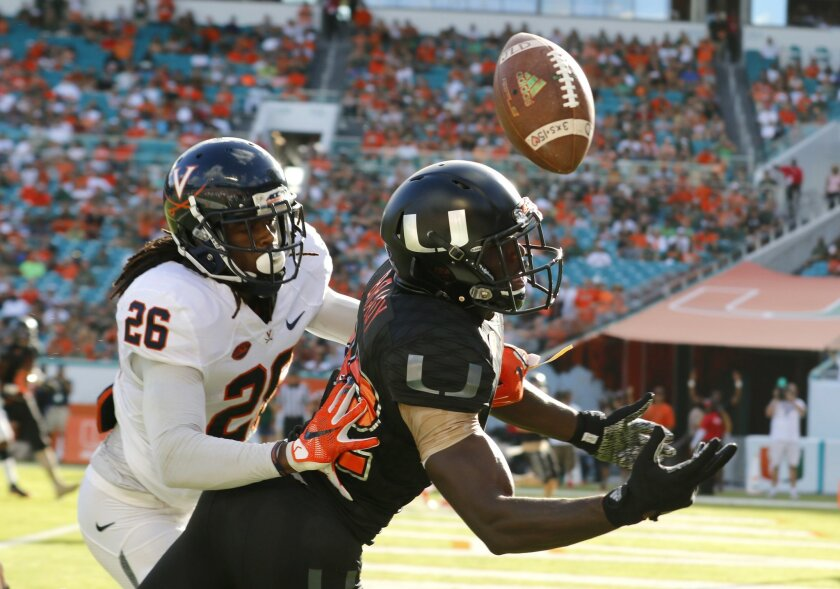 Miami wide receiver Tyre Brady (82) can't hold on to a pass in the end zone under pressure from Virginia cornerback Maurice Canady (26) in the first half of an NCAA college football game, Saturday, Nov. 7, 2015, in Miami Gardens, Fla. (AP Photo/Joe Skipper)