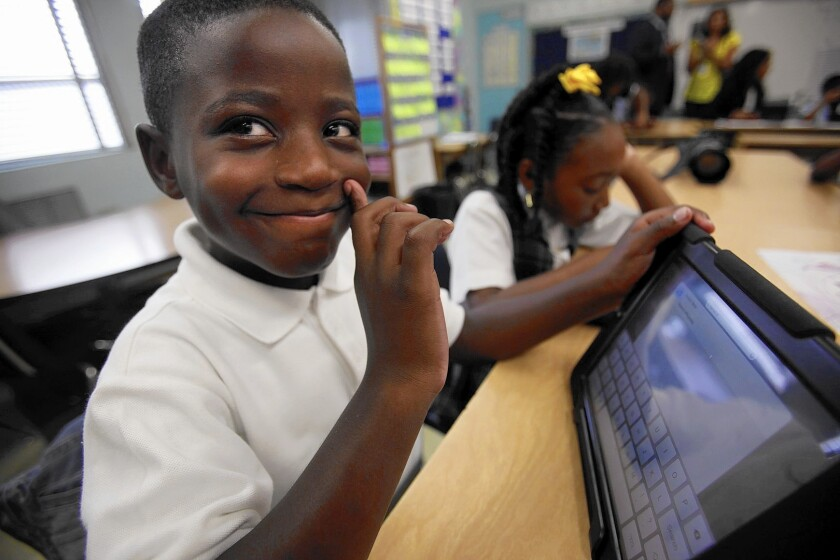 A student smiles as he explores one of the new iPads provided by L.A. Unified to 47 schools in the district. The goal was to give every student, teacher and campus administrator a device.