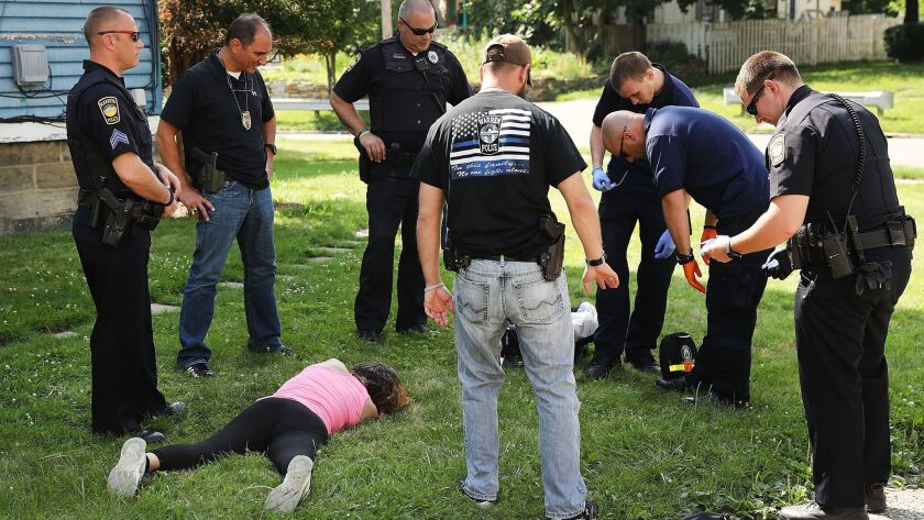 Medical workers and police treat a woman who has overdosed on opioids on July 14 in Warren, Ohio.