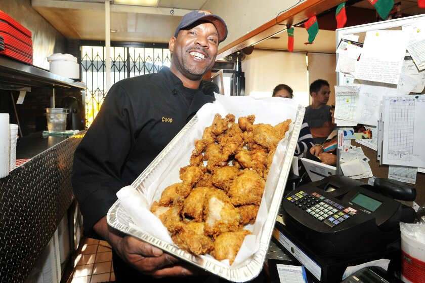 Owner Bradrick Cooper shows off some fried chicken at Coop's West Texas BBQ.