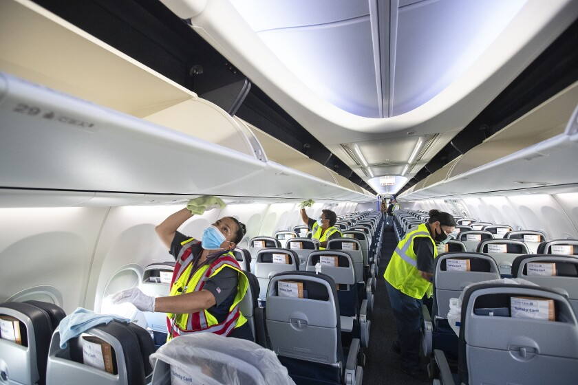 Workers clean the inside of a plane cabin