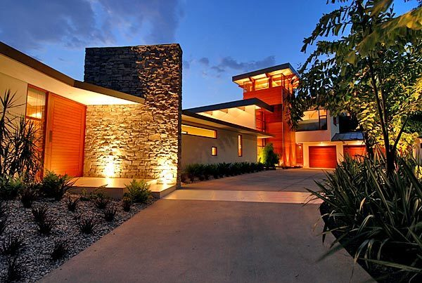 A wood exterior accent at the entry ties into the wooden doors of the three-car garage of the Bel-Air contemporary.