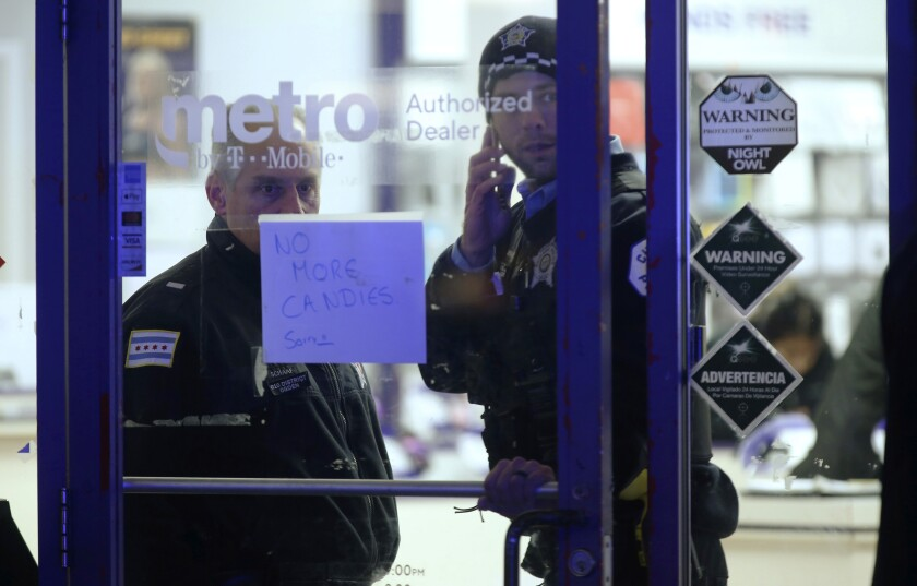 A police supervisor and officer stand inside a cellphone store where a 7-year-old girl was shot while trick-or-treating in Chicago on Thursday.