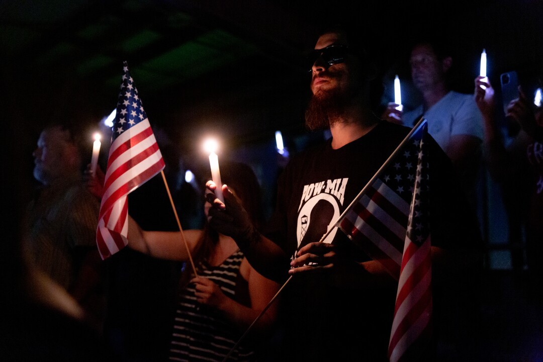 A man in a POW-MIA T-shirt holds a flag and a candle in the dark among other people.