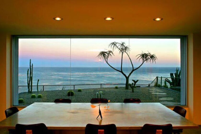 A clean simplicity rules the Malibu home of artist Charles Arnoldi and wife, Katie, a novelist. He designed the house as well as most of its furniture, including an aluminum dining table topped with a small Calder sculpture. Arnold Schwarzenegger liked the table so much that he commissioned one for himself, Charles says. Outside the window is the silhouette of an aloe tree, backed by a sunset over the Pacific.
