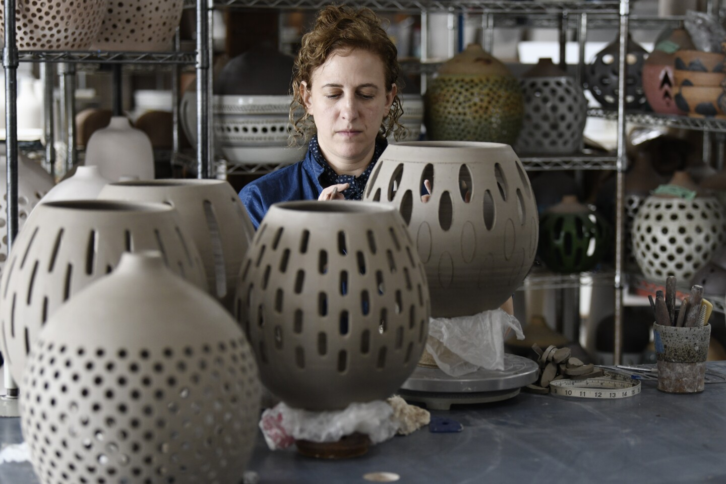 Ceramicist and artist Heather Levine works on a pendant in her studio.