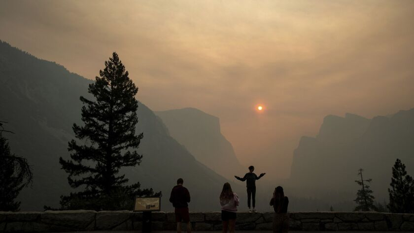 Hannah Whyatt poses for a friend's photo as smoke from the Ferguson fire fills Yosemite Valley, Wedn