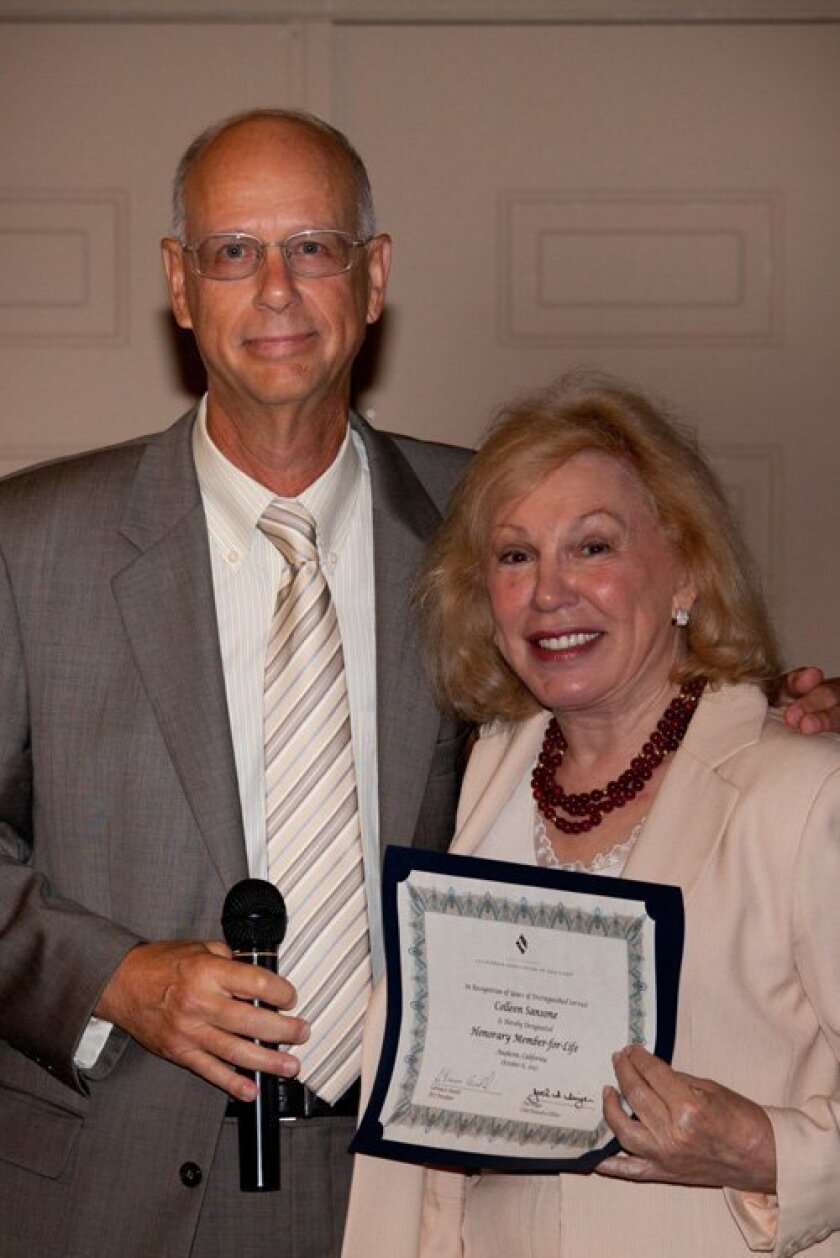 Robert Pahkle, board chairman of North San Diego California Association of Realtors, presents Colleen Sansone with the Honorary Member-for-Life Award by the California Association of Realtors. Courtesy photo