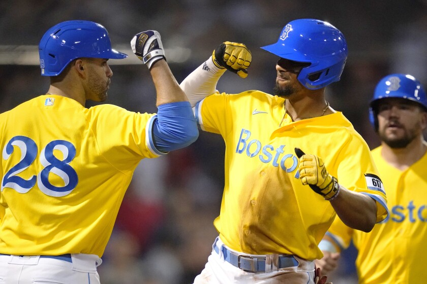 Boston Red Sox's Xander Bogaerts, right, is congratulated by J.D. Martinez (28) after his two-run home run in the fifth inning of a baseball game against the New York Mets at Fenway Park, Tuesday, Sept. 21, 2021, in Boston. (AP Photo/Charles Krupa)