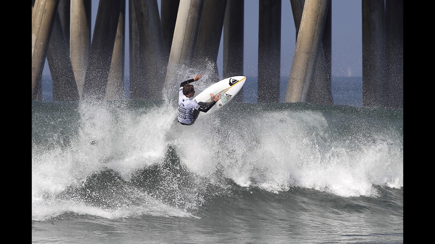 Huntington Beach's own Griffin Foy goes high up off the lip of a head-high wave during opening round of the Vans US Open of Surfing Pro Junior in Huntington Beach on Saturday. Foy took second in the heat to advance.