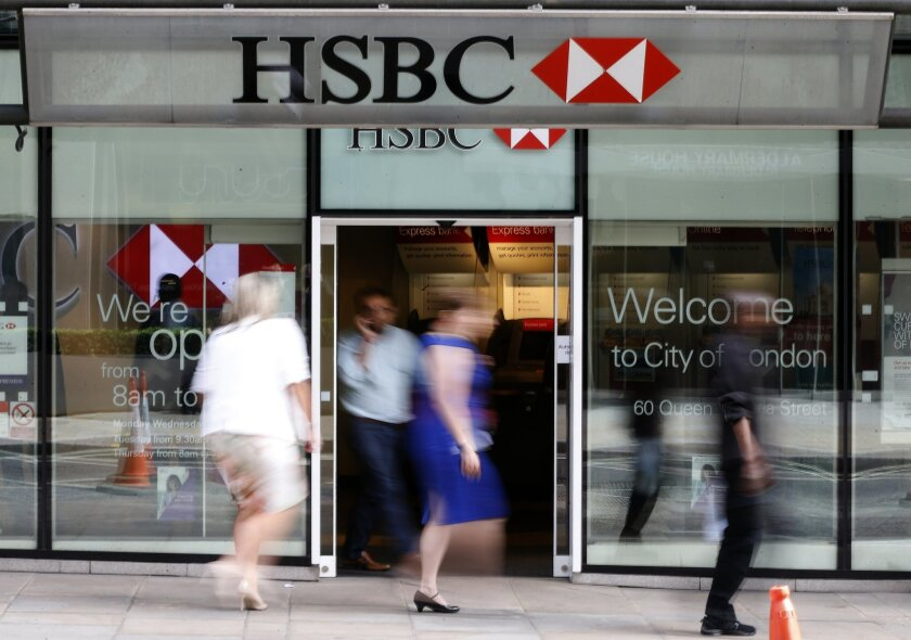 """FILE - This is a Friday, Aug. 28, 2015 file photo of people as they walk past a branch of HSBC bank in London. HSBC warned of a """"bumpier"""" global financial outlook thanks to China's slowing economy, as it reported Monday, Feb. 22, 2016, that profit dipped slightly last year. Europe's biggest bank posted a net profit of $13.5 billion for 2015, down 1.2 percent from the year before. (AP Photo/Frank Augstein, File)"""