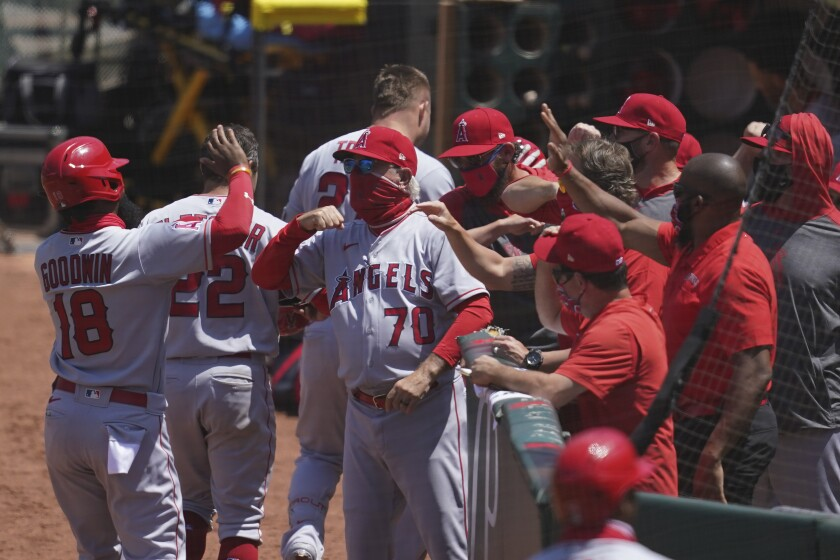 Angels manager Joe Maddon, center, greets players after a three-run home run by Mike Trout.