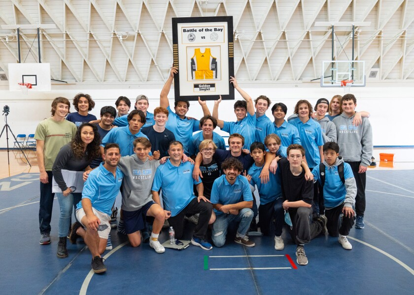 The Corona del Mar wrestling team celebrates after beating Newport Harbor for the Wave League title.