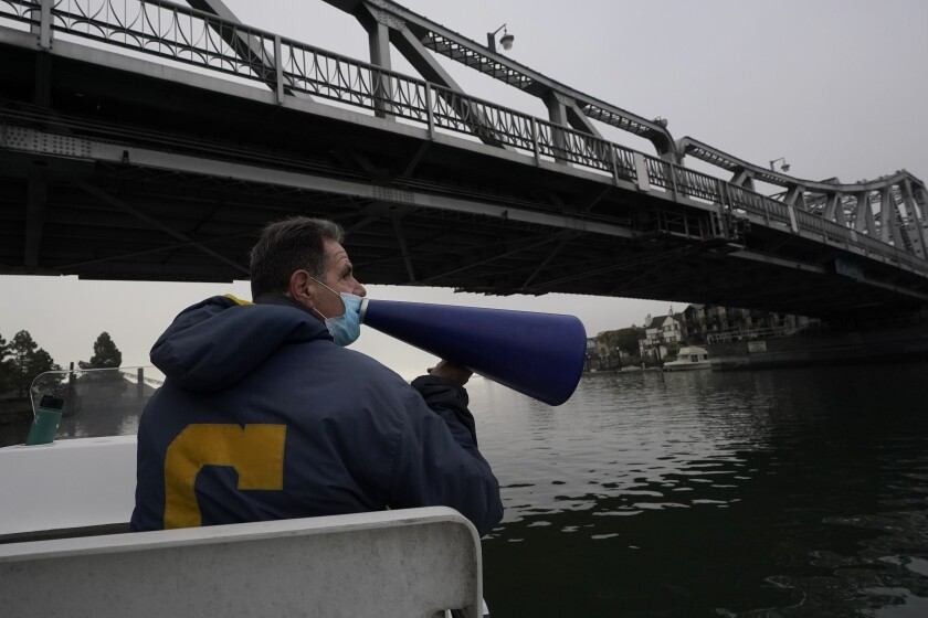 Coach Mike Teti speaks into a megaphone toward rowers practicing in the Oakland Estuary in Oakland, Calif., Thursday, Nov. 19, 2020. Nearly two dozen U.S. men's rowers signed on to keep training for another year after the Tokyo Olympics were delayed until 2021. Teti, a three-time Olympian himself, is thrilled the group stuck together. (AP Photo/Jeff Chiu)