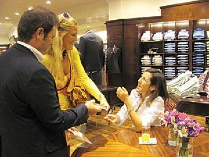 A couple offers author Lisa Birnbach a book to sign. Photos Susan DeMaggio