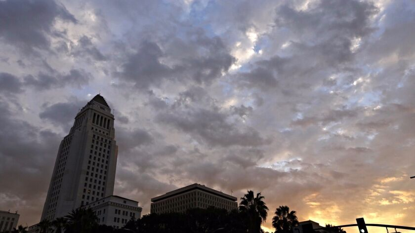 The sun rises over City Hall in downtown Los Angeles on Friday as clouds move into the L.A. Basin with a threat of rain as a storm front promises light rain for parts of the Southland.