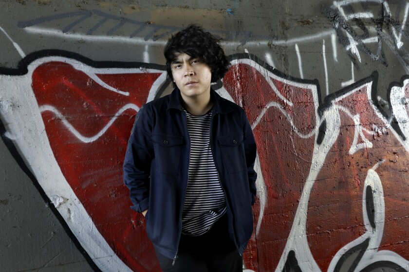 Ed Maverick stands, hands in pockets, in front of a graffitied concrete wall.
