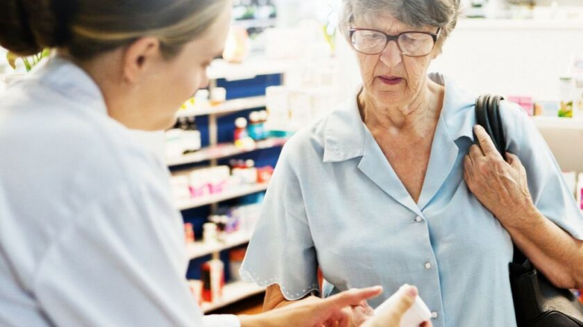 Female pharmacist explaining medication to senior woman customer