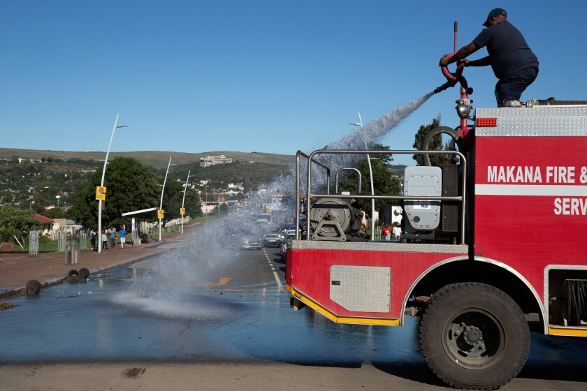 A fire brigade washes away feces that was dumped on the main road ahead of President Cyril Ramaphosa's visit to Makhanda on Freedom Day.
