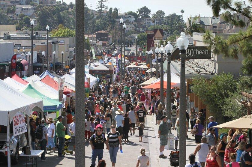 People and vendor booths crowd La Mesa Boulevard at La Mesa's Oktoberfest.