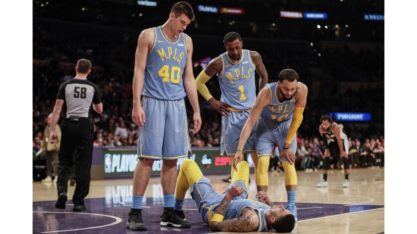 A visibly exhausted Kyle Kuzma is offered a hand by Lakers teammate Tyler Ennis, right, with Kentavious Caldwell-Pope and Ivaca Zubac, after he was fouled on a driving layup against the Spurs in overtime.