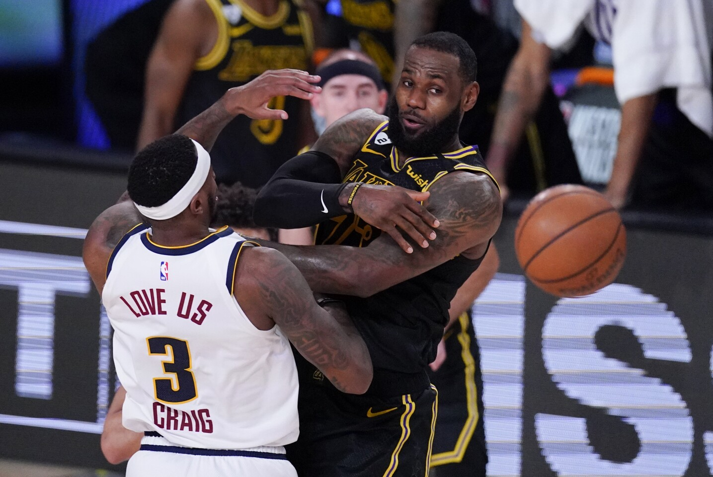 Los Angeles Lakers' LeBron James passes over Denver Nuggets' Torrey Craig (3) during the first half of an NBA conference final playoff basketball game Sunday, Sept. 20, 2020, in Lake Buena Vista, Fla. (AP Photo/Mark J. Terrill)