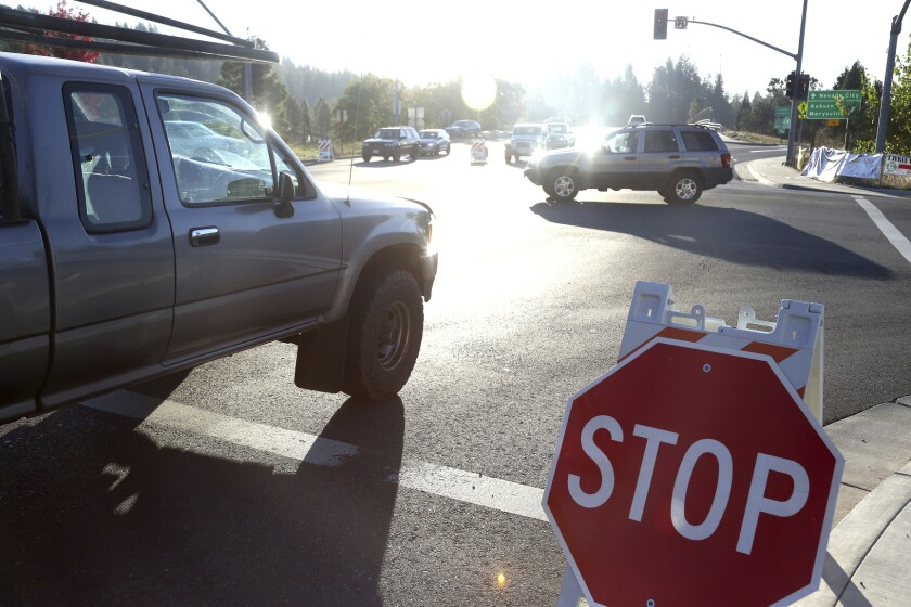 Drivers navigate through an intersection with signals out and stop signs put in place during the power shutdown in Grass Valley.