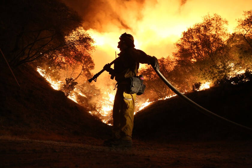 Andrew Dodds mans the water line as firefighters work to start a backfire to contain the Butte fire on Fricot City Road near Sheeps Ranch, Calif., on Sept. 12.