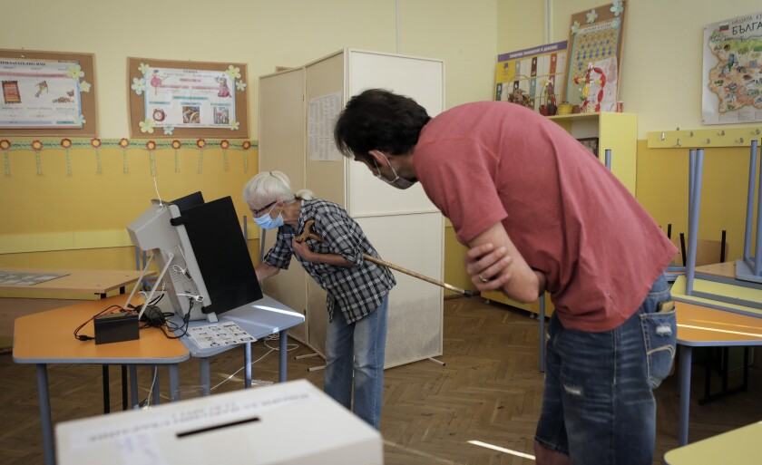 An elderly Bulgarian woman is assisted by an election commission member during her vote at a polling station in Sofia, Sunday, July 11, 2021. Bulgarians are voting in a snap poll on Sunday after a previous election in April produced a fragmented parliament that failed to form a viable coalition government. (AP Photo/Valentina Petrova)