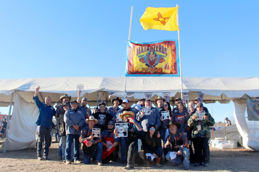 The Rio Grande Matanzeros in front of their booth, along with their trophies; Guardian is kneeling a