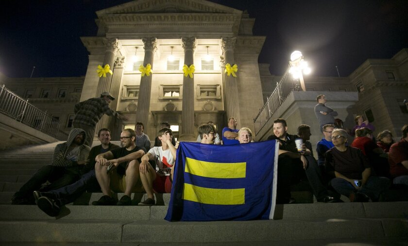 FILE - In this May 13, 2014, file photo, same-sex marriage supporters gather on the steps of the Idaho Statehouse in Boise after U.S. Magistrate Judge Candy Dale ruled earlier in the day that Idaho's ban on gay marriage is unconstitutional. The same-sex marriage debate returns Monday Sept. 8, 2014, to the same San Francisco federal appeals court that has already issued two significant rulings in support of gay weddings. The 9th U.S. Circuit Court of Appeals will consider separate lawsuits stemming from gay marriage bans in Idaho, Nevada and Hawaii. So far, 19 states and Washington D.C. now allow gay marriages even though the U.S. Supreme Court has yet to directly rule on whether states can impose bans. (AP Photo/The Idaho Statesman, Kyle Green, File)