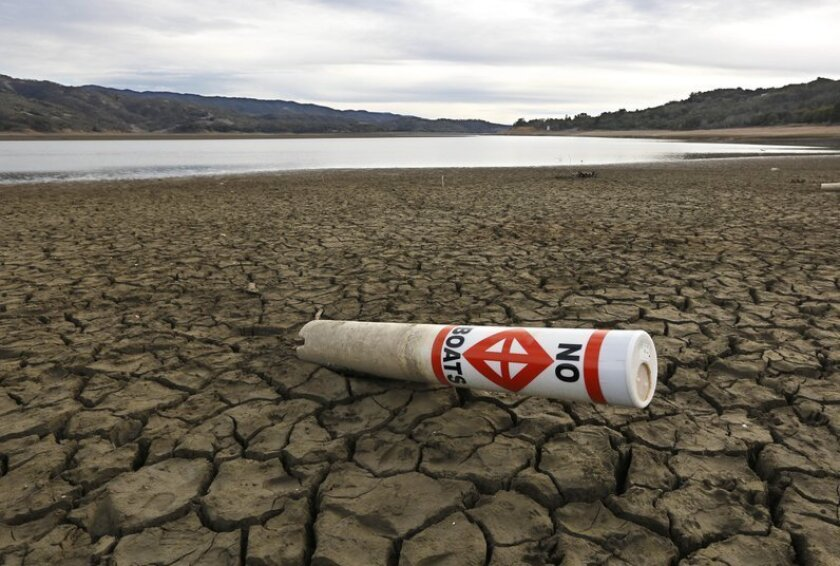 FILE -- In this Feb. 4, 2014 file photo, a warning buoy sits on the dry, cracked bed of Lake Mendocino near Ukiah, Calif.  The Legislature will revisit overhauling an  $11.1 billion water bond measure  that is scheduled to go before voters in November, when they return from a month long summer rece