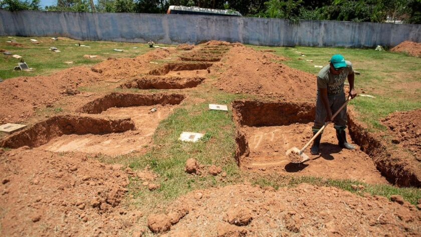 A worker digs graves Tuesday for victims of Friday's collapse of a waste dam in southeastern Brazil.
