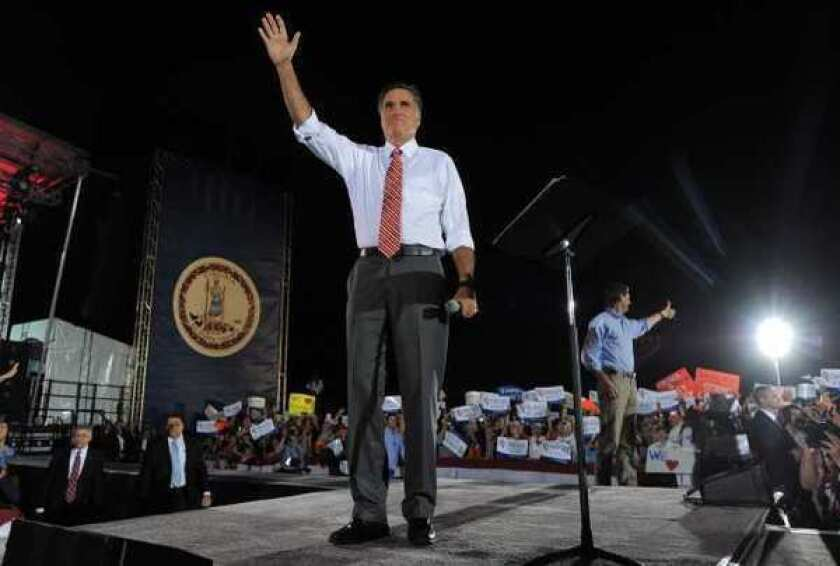 Mitt Romney and running mate Paul Ryan, in background, at a rally in Fishersville, Va.