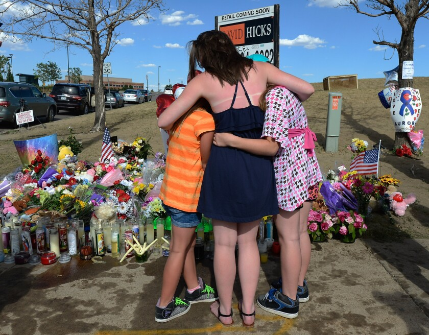 Sisters hug at a makeshift memorial across the street from the Century 16 movie theater the day after a gunman killed 12 people and injured 59 in Aurora, Colo.