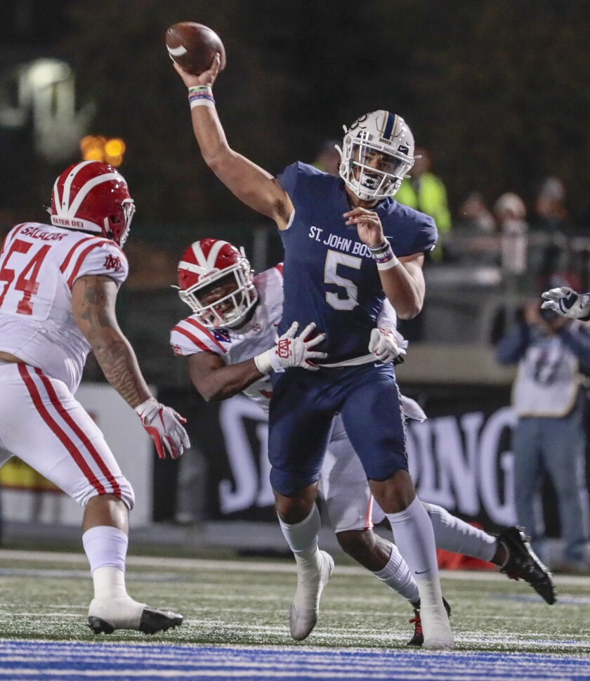 Mater Dei defenders pressure St. John Bosco quarterback DJ Uiagalalei during the Southern Section Division 1 championship game Nov. 30, 2019, at Cerritos College.